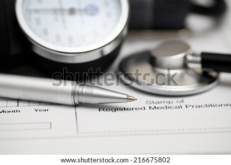 Blood Pressure Gauge (shygmomanometer, stethoscope, cuff) and ballpoint pen on medical records. Focus on ballpoint pen. Closeup.