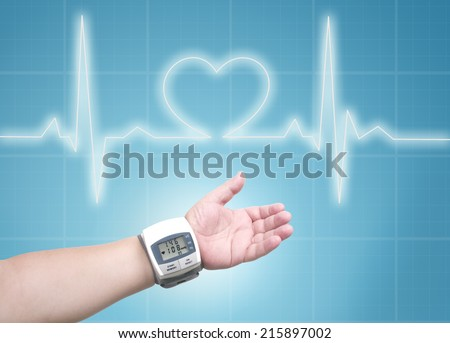 blood pressure meter on man wrist, ecg line background - stock photo