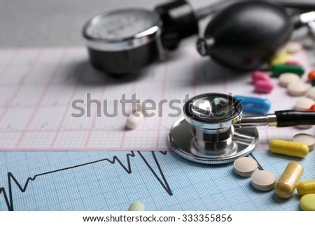Blood pressure meter, pills and stethoscope, on grey background - stock photo