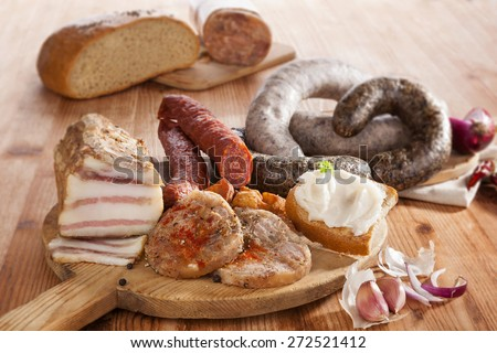 Blood sausage, rice sausage, head cheese, garlic, onion beer and bread on wooden kitchen board on wooden background. Traditional pork meat eating. - stock photo
