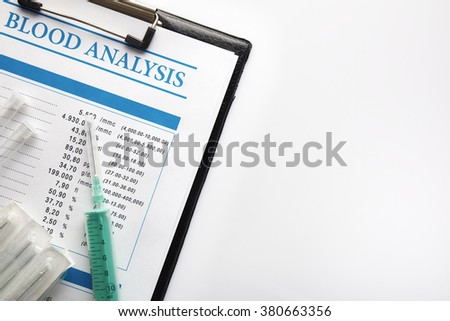Blood test report in a black folder with vials and syringe over white glass table. Horizontal composition. Top view. - stock photo