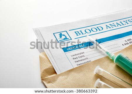 Blood test report in a brown envelope with vials and syringe over white glass table. Horizontal composition. Elevated view.