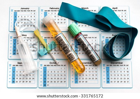 blood tube, urine test, needle and tourniquet on the bottom of an appointment calendar in lab table / equipment for analysis on the daily schedule - stock photo