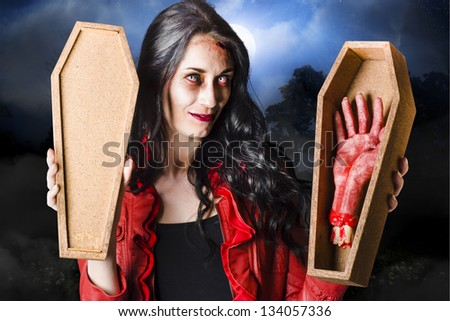 Bloodthirsty dead sexy brunette zombie woman standing at a night cemetery location in moonlight and mist holding open casket and severed hand in a welcome to your tomb concept - stock photo