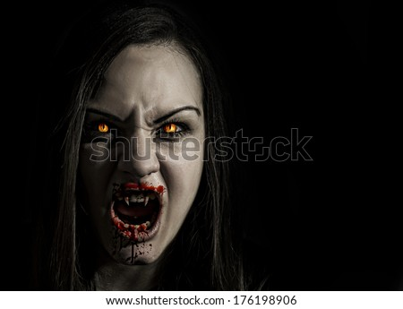 Bloodthirsty female vampire with angry expression and bloody mouth isolated on black background - stock photo