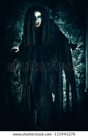 Bloodthirsty vampire flying at the night cemetery in the mist and moonlight. - stock photo