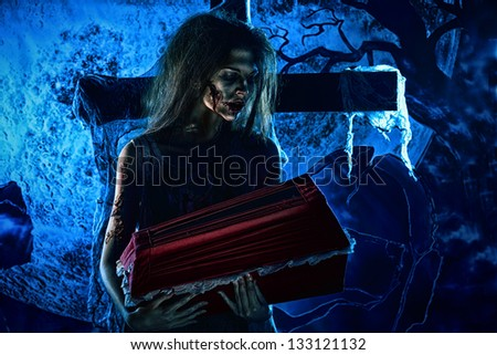 Bloodthirsty witch standing at the night cemetery and holding a coffin. - stock photo