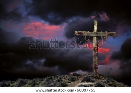 Bloody empty Christian cross against angry cloudy sky representing the immediate aftermath of the crucifixion of Jesus Christ. - stock photo