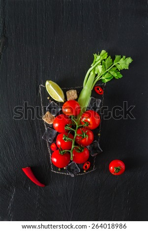 Bloody Mary cocktail ingredients - cherry tomatoes, celery, chili, lime, sugar, ice on dark stone background with glass painted in chalk, top view - stock photo