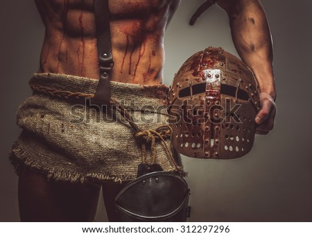 Bloody muscular torso and helmet of gladiator. - stock photo