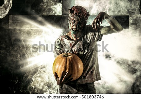Bloody zombie man with brains out holding halloween pumpkin. Horror. Halloween.