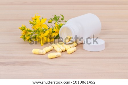 blooming and dried St. John's wort and white container with medicines  on wooden ground