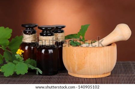 Blooming Celandine with medicine bottles on table on brown background - stock photo