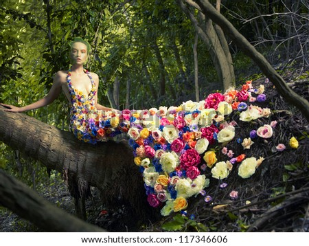 Blooming gorgeous lady in a dress of flowers in the rainforest - stock photo