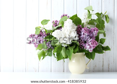 Blooming lilac flowers in the vase on wall paneling background