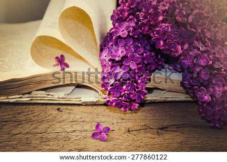 Blooming lilacs and old books on a wooden table. - stock photo