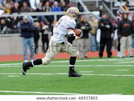 BLOOMSBURG, PA - NOVEMBER 6: Kutztown University kick returner Josh Mastromatto heads off upfield with the ball in a football game November 6, 2010 in Bloomsburg, PA - stock photo