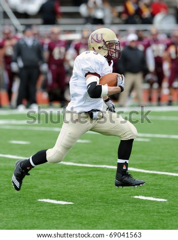 BLOOMSBURG, PA - NOVEMBER 6: Kutztown University kick returner Josh Mastromatto heads off upfield with the ball in a football game on November 6, 2010 in Bloomsburg, PA - stock photo