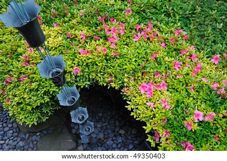 blossom azalea flowers around hanged up traditional metallic bells used for rain waters way-out in japanese zen garden - stock photo