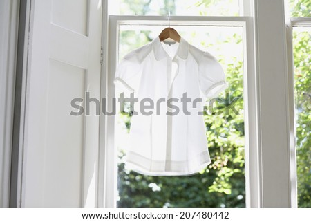 Blouse on hanger at domestic window - stock photo