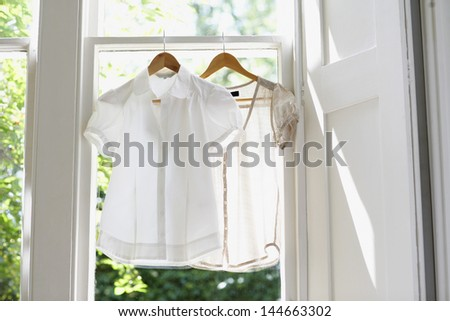 Blouses on hangers at domestic window - stock photo