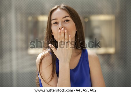 Blow kiss, young caucasian female brunette model, indoor background  - stock photo