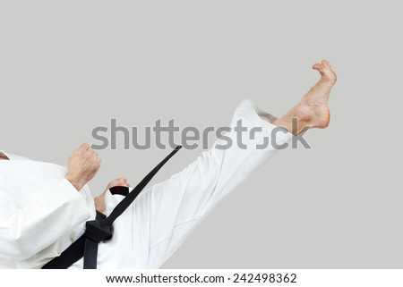 Blow Mae-geri in the performance of an athlete with a black belt - stock photo