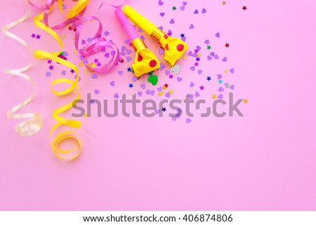 Blowers, streamers and confetti on pink background - stock photo
