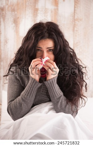 Blowing her nose. Young beauty with scarf on her neck sitting in bed with tissue and sneezing in her country house - stock photo