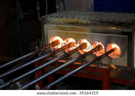 Blowpipes in a furnace in a glass factory - stock photo