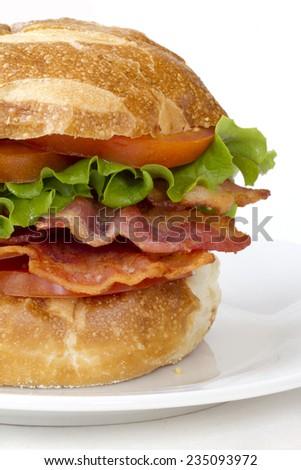 BLT sandwich on pretzel bun. Isolated on white. - stock photo