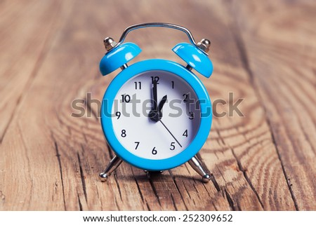 blue alarm clock on a wooden table - stock photo