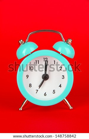 Blue alarm clock on red background - stock photo
