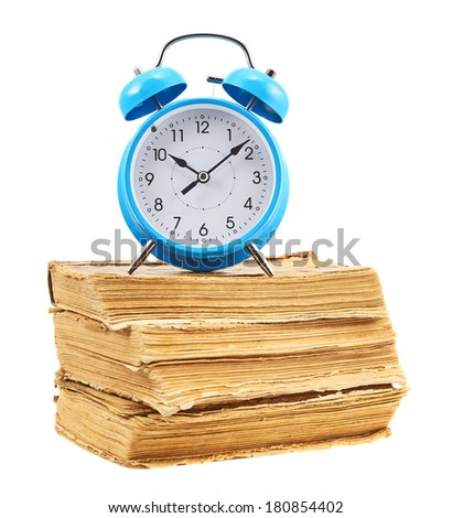Blue alarm clock on the stack of books isolated over the white background - stock photo