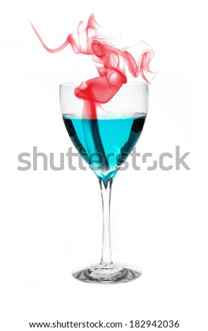 Blue alcohol in a glass with red smoke implying evaporation or heat. - stock photo