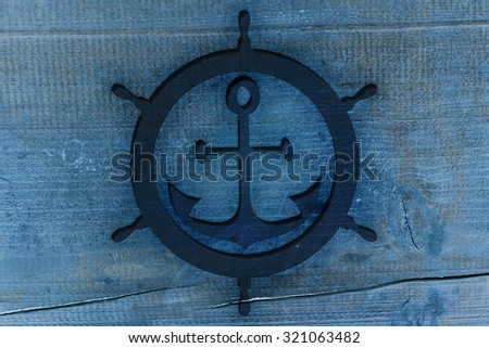 Blue anchor and rudder icon carved in the wood, texture for nautical design. - stock photo