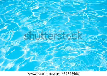 Blue and bright water surface in swimming pool with sun reflection