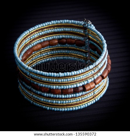 Blue and brown  beaded bracelet on black background - stock photo