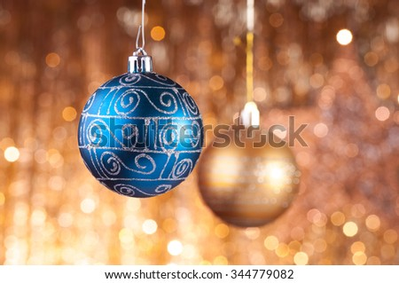 Blue and gold christmas baubles on background of defocused golden lights. - stock photo