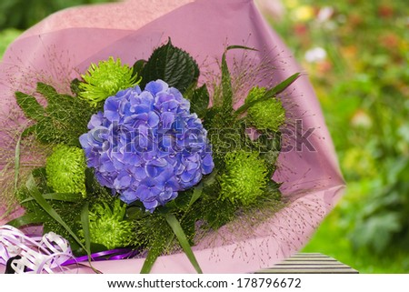 Blue and green bouquet of flowers wrapped in paper with summer garden background - stock photo