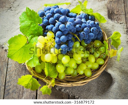 blue and green grapes in a basket on a wooden background toning - stock photo