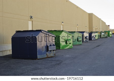 Blue and green industrial garbage bins lined up outside along commercial building