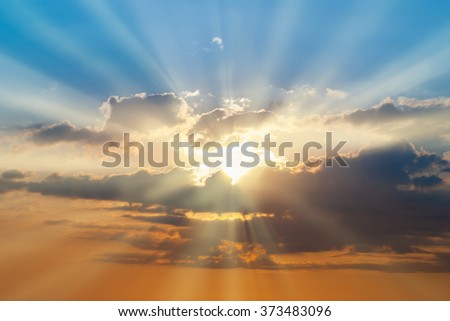 Blue and orange sunset sky with rays of sun. Natural landscape for background - stock photo