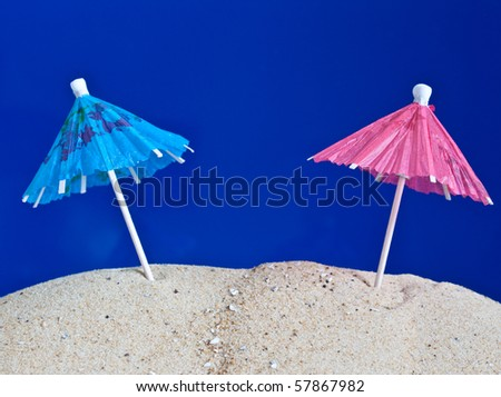 blue and pink cocktail umbrellas standing in the sand - stock photo