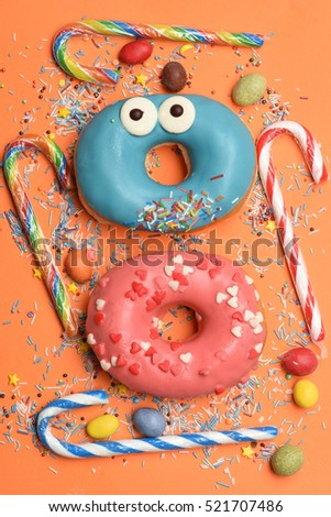Blue and pink funny glazed donuts with sprinkles, striped caramel candies, colorful dragee with raisins or peanuts inside on orange background