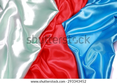 Blue and red and light green Silk cloth of abstract backgrounds or wavy folds or satiny silk texture satin velvet material or elegant wallpaper design curve. - stock photo
