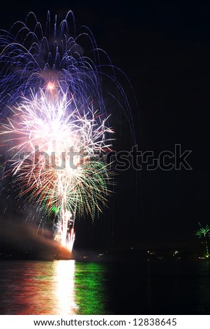 Blue and red fireworks launched from boat. Attention, small noise in the dark parts of the image. - stock photo