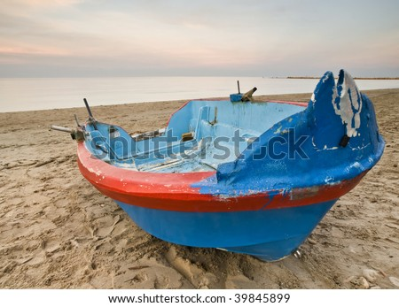 Blue and red fishing boat on the sand of a lonely beach, with the warm light of sunset - stock photo