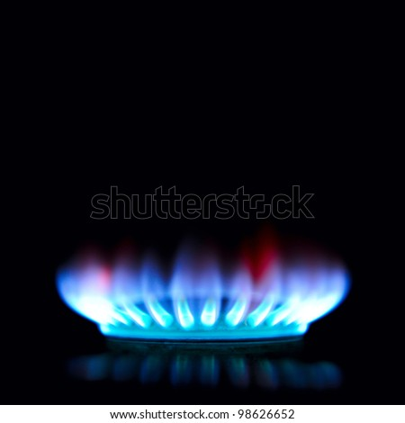 Blue and red gas stove in the dark - stock photo