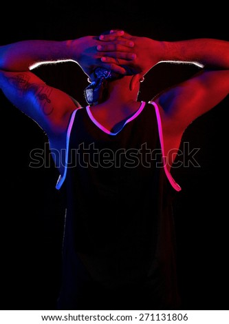 blue and red lights from a police siren on a criminal surrendering.  The red and blue lights simulate a police siren.  Low key exposure to make color gels pop. - stock photo
